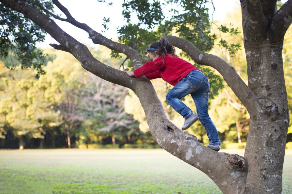 girl climbing up tree.