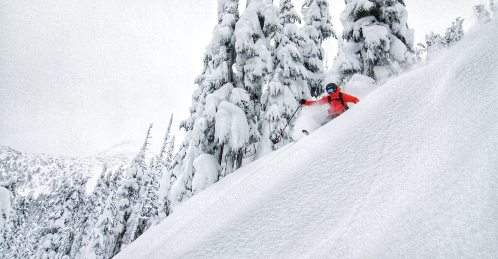 A Rippin Chix skier goes down a steep and deep run.