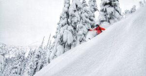 A Rippin Chix skier goes down a steep and deep run.