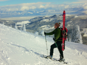 Man snowshoeing up a snowy slope, wearing backpack with skis strapped to it.