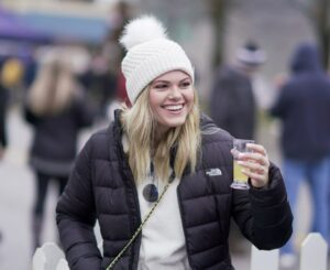 Woman wearing winter pom-hat and holding a glass of beer at Winterfest in Chelan, Washington.