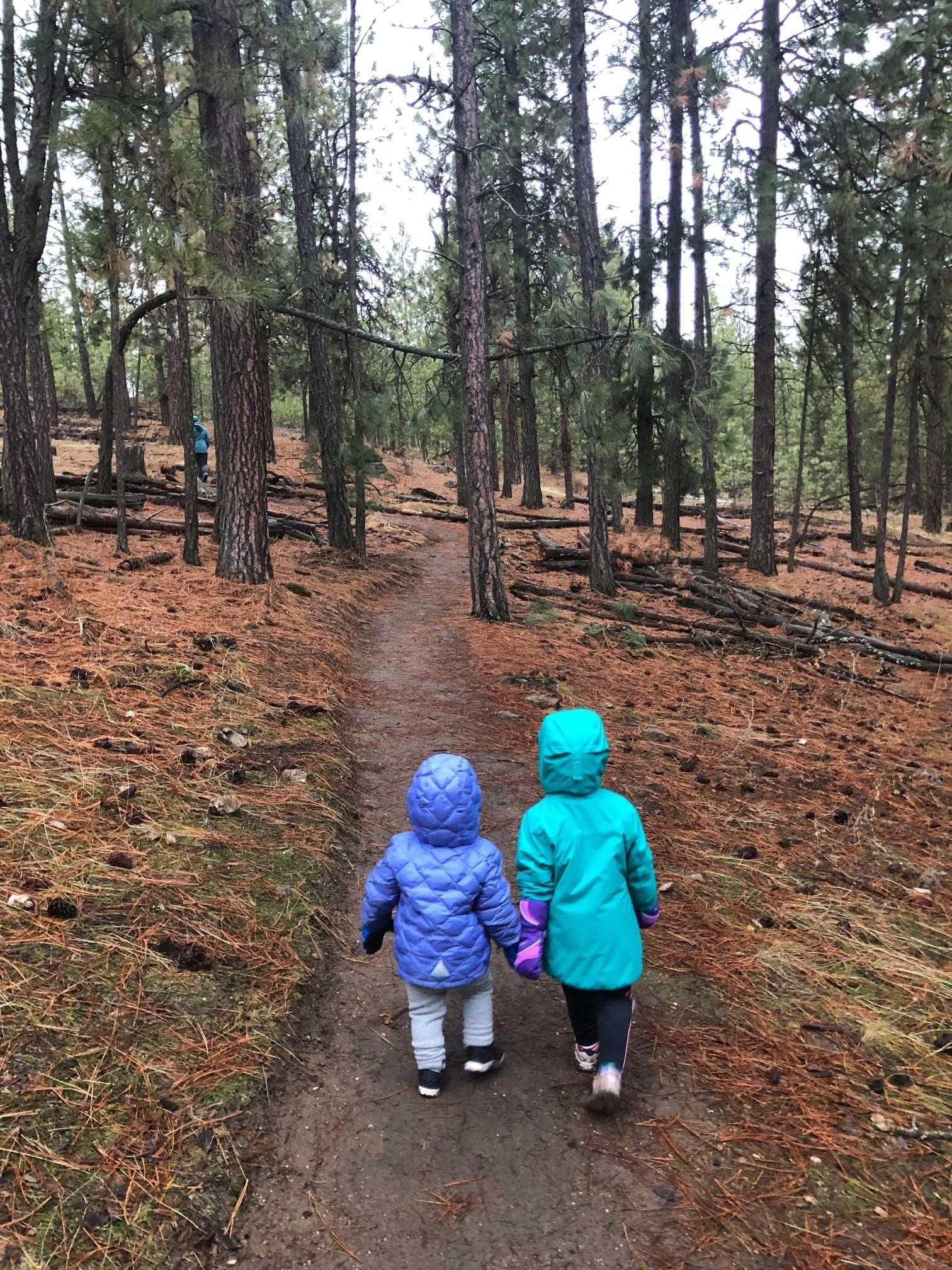 Two little girls walking together, holding hands, along a trail in Dishman Hills Natural Area.
