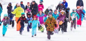 Ski kids racing through the snow.