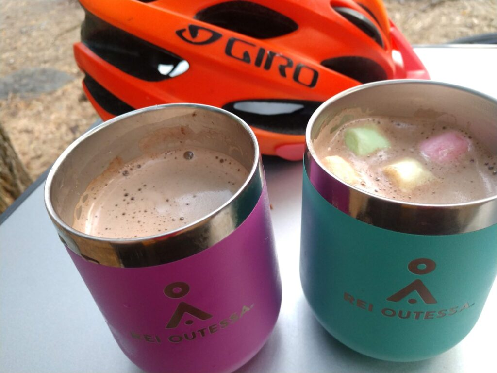 A table with two stainless steel mugs filled with hot cocoa, topped with marshmallows, and a bike helmet behind them on the tabletop.
