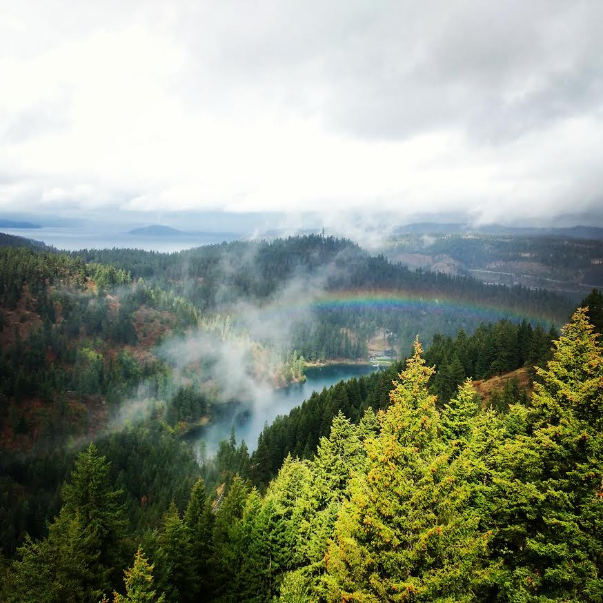 View from Timberline Adventures zipline course of of Beauty Bay at Lake Coeur d'Alene, featuring forested hillsides, wispy clouds, and a rainbow.