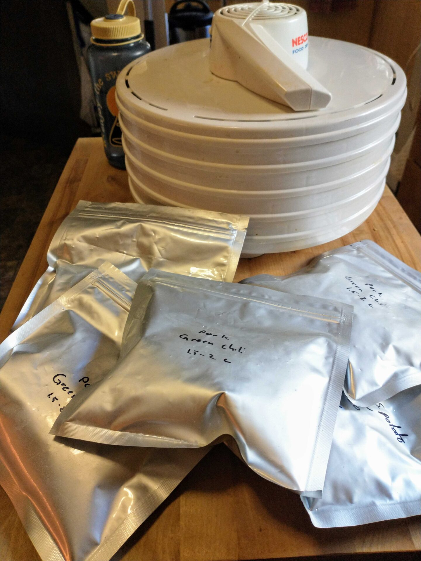 Silver mylar bags of dehydrated meals and a white-colored, circular dehydration machine.