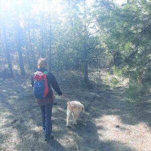 Woman hiking with her dog on a forested trail at Slavin Conservation Area.