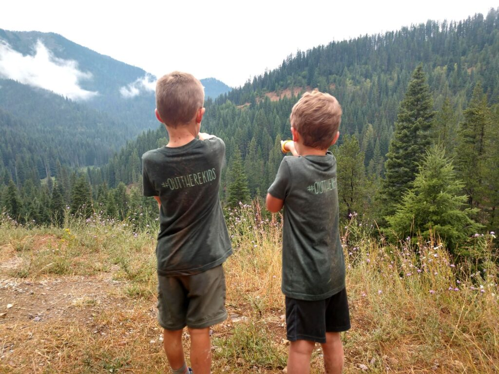 Two children wearing t-shirts that say #OutThereKids on the back, standing in a clearing and looking and pointing to the view of a forested hillside in the distance.