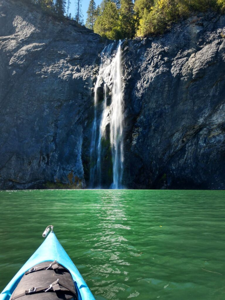 View from a kayak of waterfall, Peewee Falls, over basalt rock into the Pend Oreille River.
