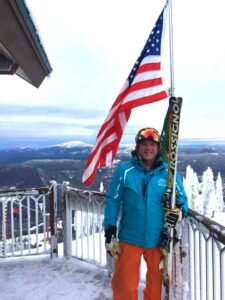 Fred Nowland in his ski gear on a resort deck with the mountain view and American flag behind him.