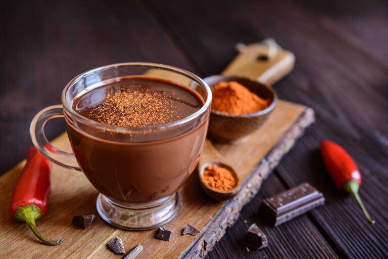 Mug of spicy hot chocolate, with chili peppers and grated chocolate.