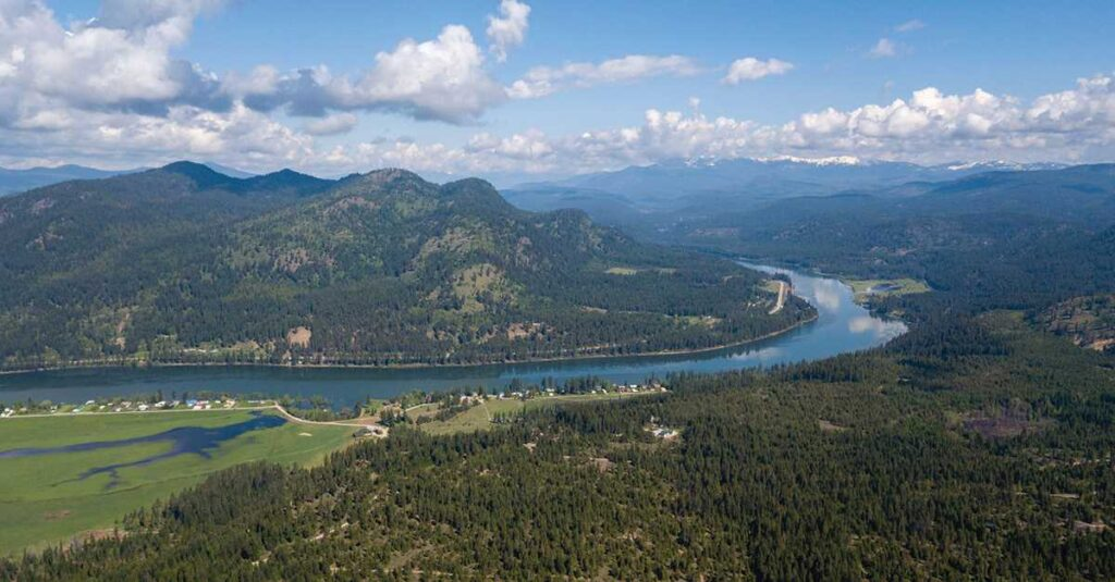 Aerial view of the Pend Oreille River valley, with forested hillsides.