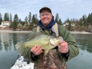 Man holding Black Crappie fish and smiling at the camera.
