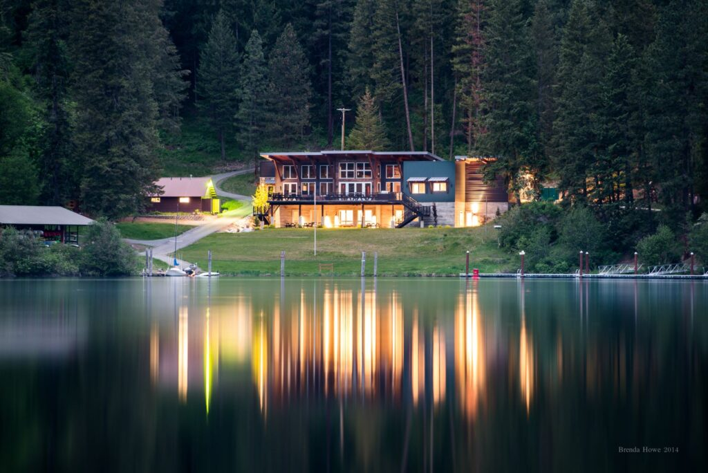 Main lodge at Camp Four Echoes at dusk with all the lights on and reflection of lodge and lights on the calm, flat surface of Lake Coeur d'Alene.
