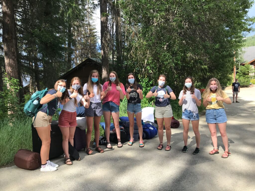 Happy teenage girls at Camp Spalding during summer 2020, gathering in a line, looking at camera, smiling behind their COVID face masks, and giving the camera thumbs-up signs. Trees in the background.
