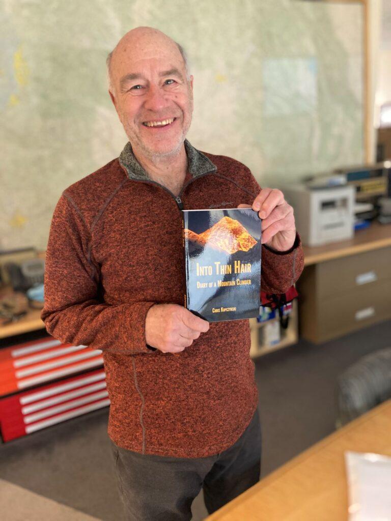 Chris Kopczynski holding his newly published book.