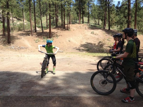 Dirt area of a park with a mountain biking instructor demonstrating a skill with a bike to a group of students.