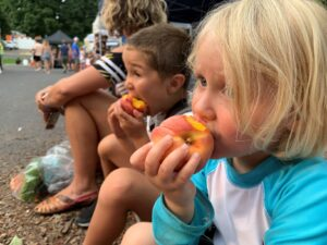 Two children sitting down and eating fresh peaches at a local farmers market.