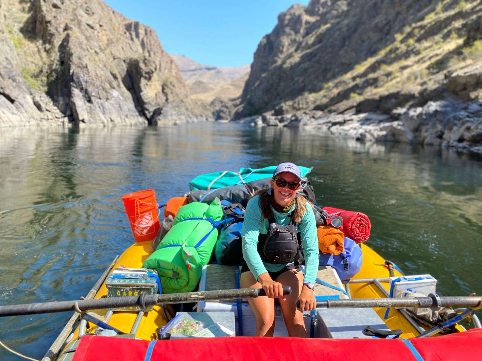 Female river raft guide, wearing a life jacket, sunglasses, and hat, sitting in a raft surrounded by colorful gear bags, with the river and rocky riverbank in the background.