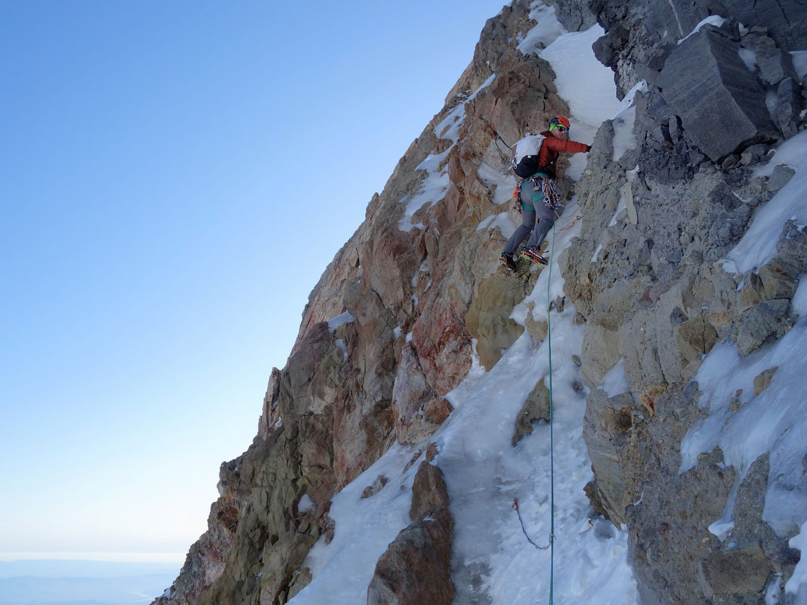 Rock climber Kyle Tarry ascending vertical mixed, rocky terrain on first pitch off Eliot Glacier -- climbing a ribbon of ice.