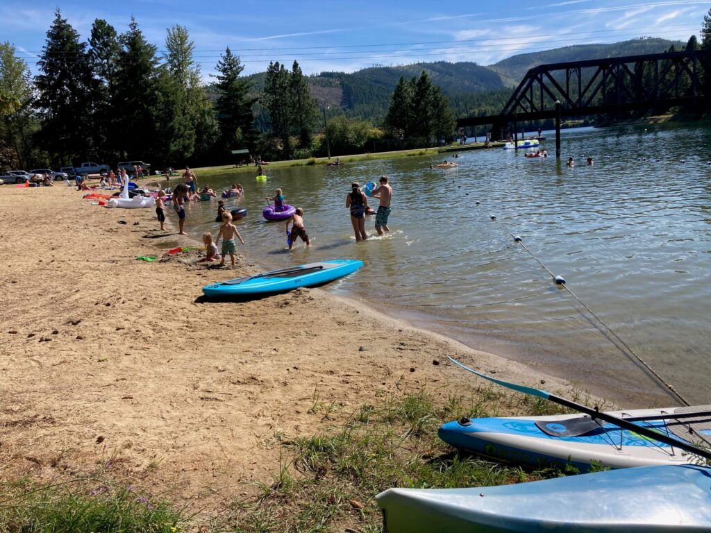 People standing on the sandy beach and in the water at Priest River Recreation Area, with kayaks and other paddling gear on the shoreline.