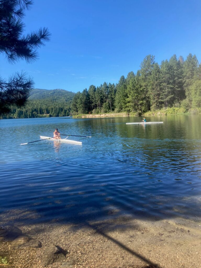 Woman kayaking towards the sandy beach at Priest River Recreation Area. Blue sky and sunshine.