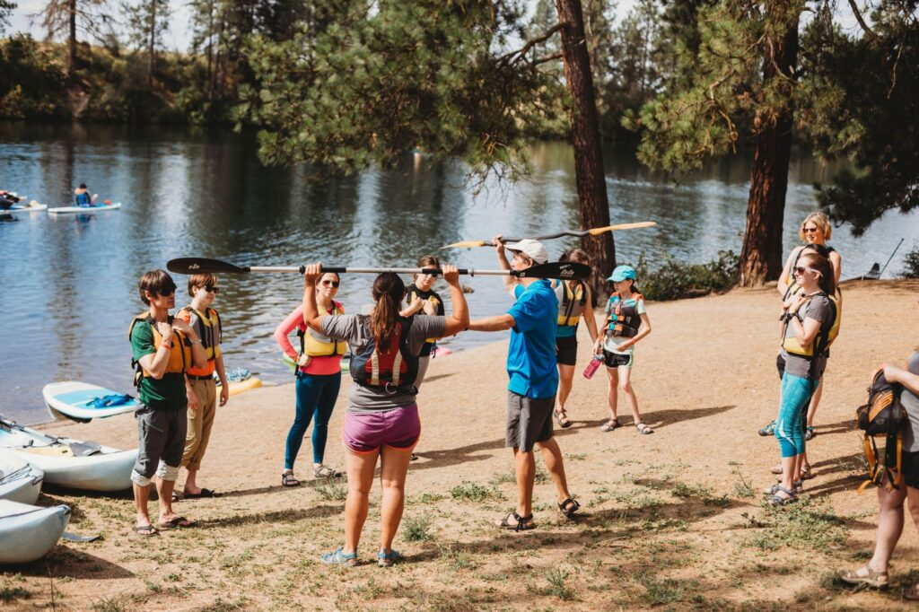 People standing on a sandy beach getting instructions on how to properly hold and use a kayak paddle during the Spokatopia Outdoor Adventures Festival in Spokane, WA.