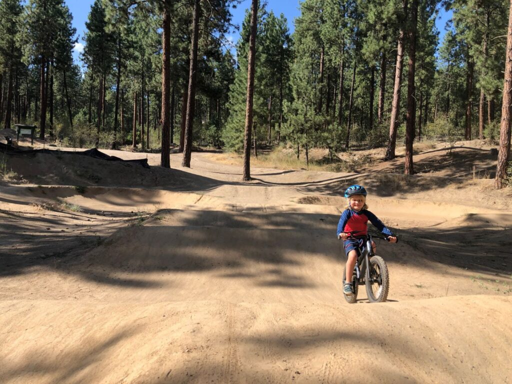 Young child riding his bike on a dirt pump track at Camp Sekani, with Ponderosa pine trees in the background.