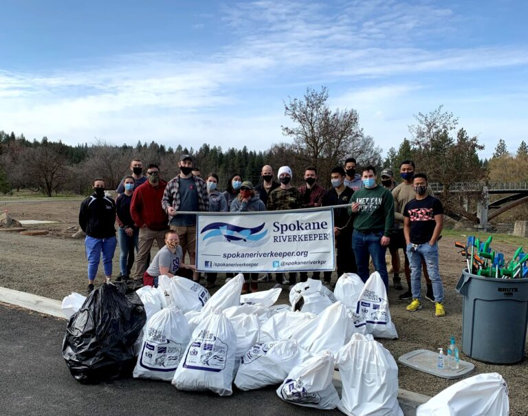 Group of volunteers for the Spokane River Clean-Up, holding a sign that says Spokane Riverkeeper, and nearly 20 huge plastic bags of trash, depicting how much debris and litter was cleaned up.