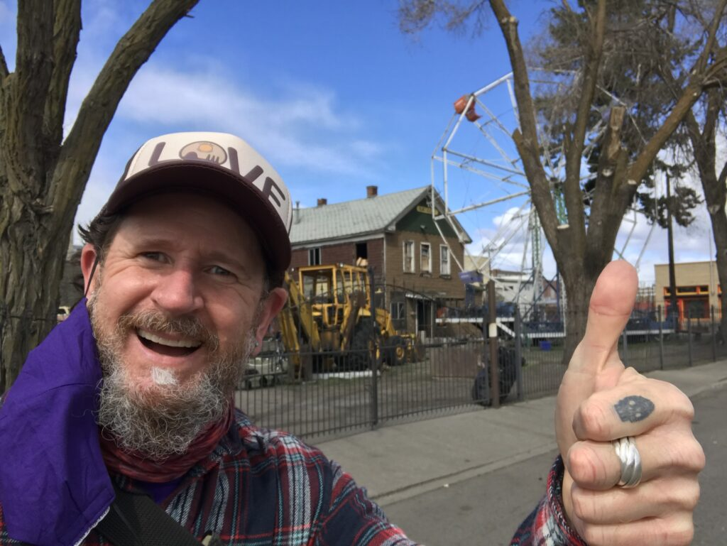 Man taking a selfie with thumbs-up sign to celebrate his walk in a new neighborhood in Spokane. House and street in background.