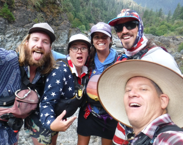 River guides wearing hats, gathered together for a funny group photo -- with wide smiles, mouths open.
