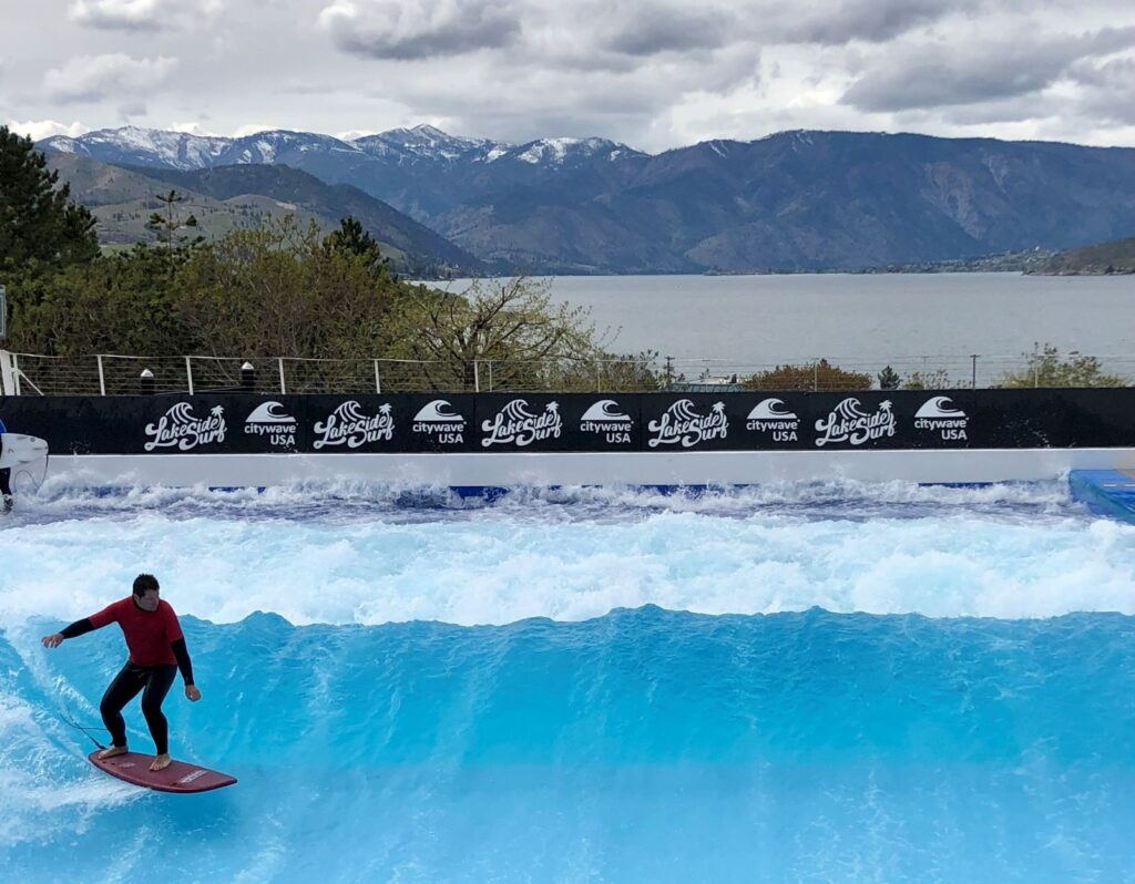 Man surfing the standing, stationary wave at Lakeside Surf, with view of Lake Chelan in the background.