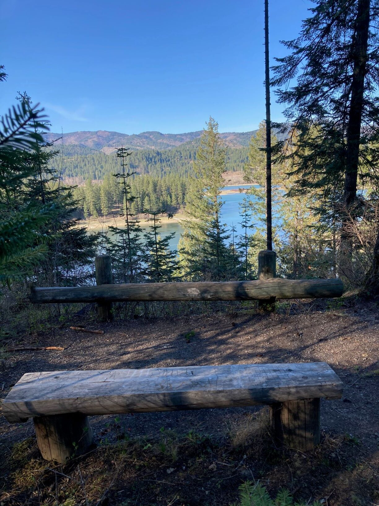 Viewpoint along Wolf Trails, with a wooden bend and trees, overlooking the Pend Oreille River with distant mountain slopes.
