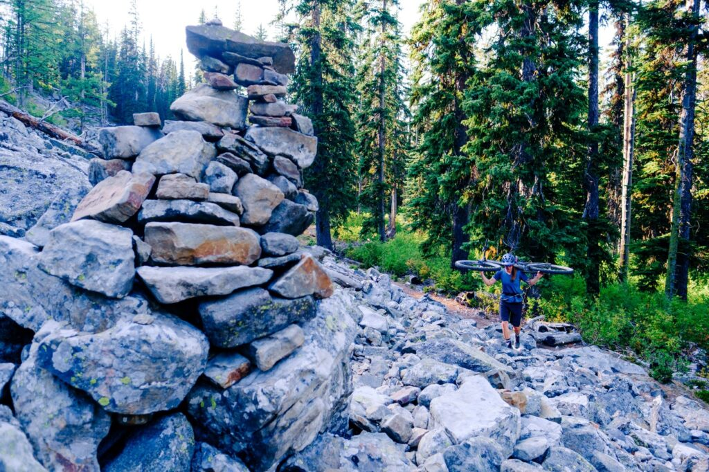 Woman carrying her mountain bike over her shoulders as she hikes over a rocky trail across a talus slope.