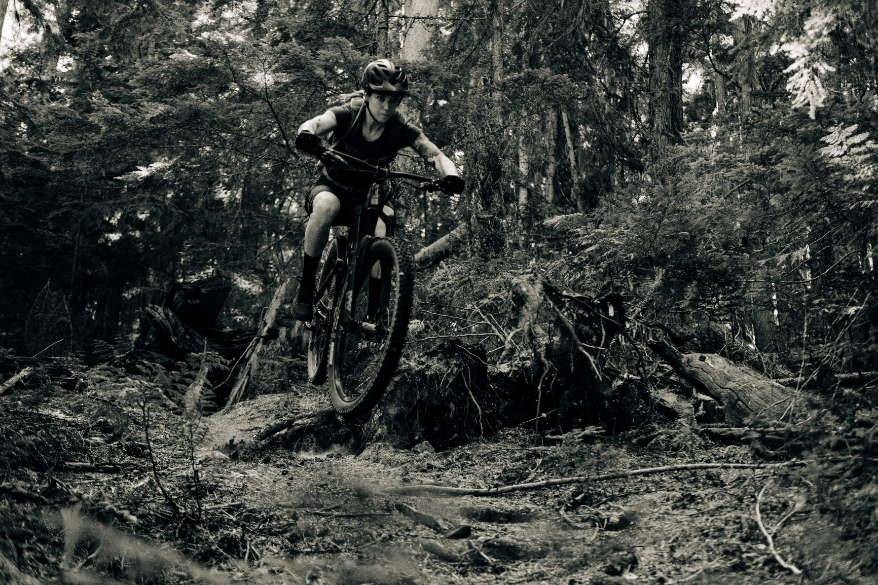 Woman mountain biking on a rugged, forested dirt trail in the Yaak wilderness of northwest Montana.
