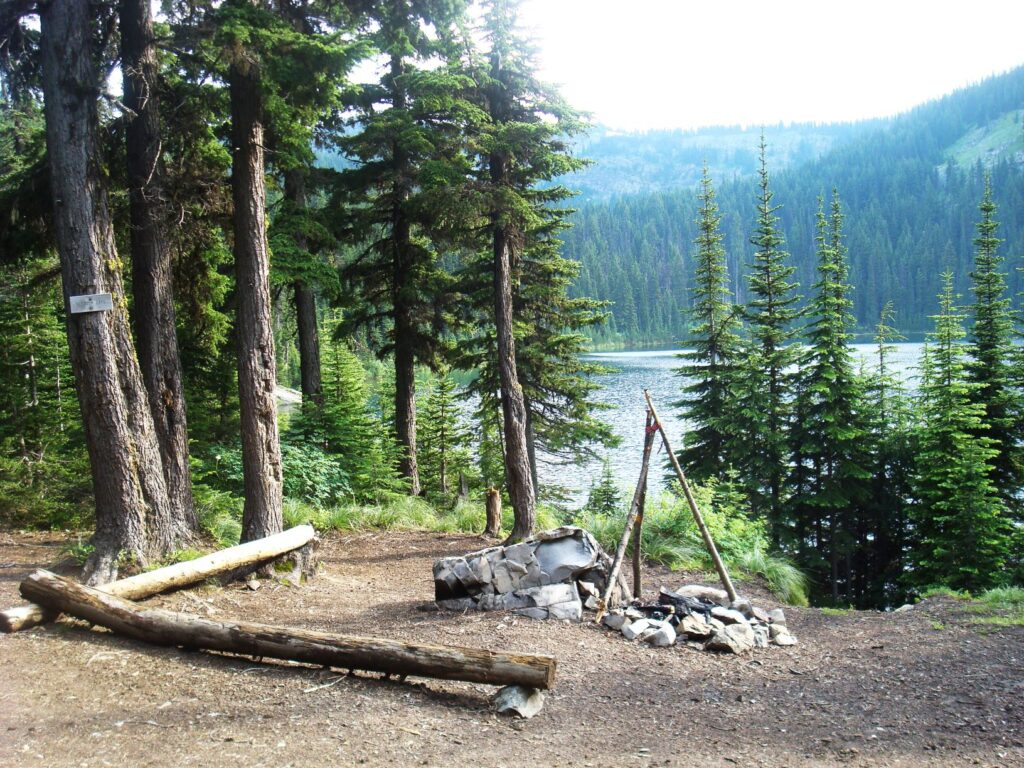 Blossom Lake campsite with rock campfire ring with view of lake and trees.