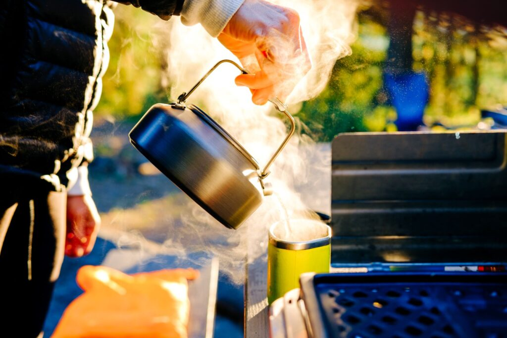 Campsite kitchen with a person pouring a kettle of hot, steamy .water into a mug