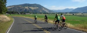 Cyclists riding in Colville, Wash., along a rural road.