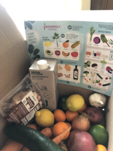 Box of vegetables and lemons and other food items from Imperfect Foods subscription box delivery.