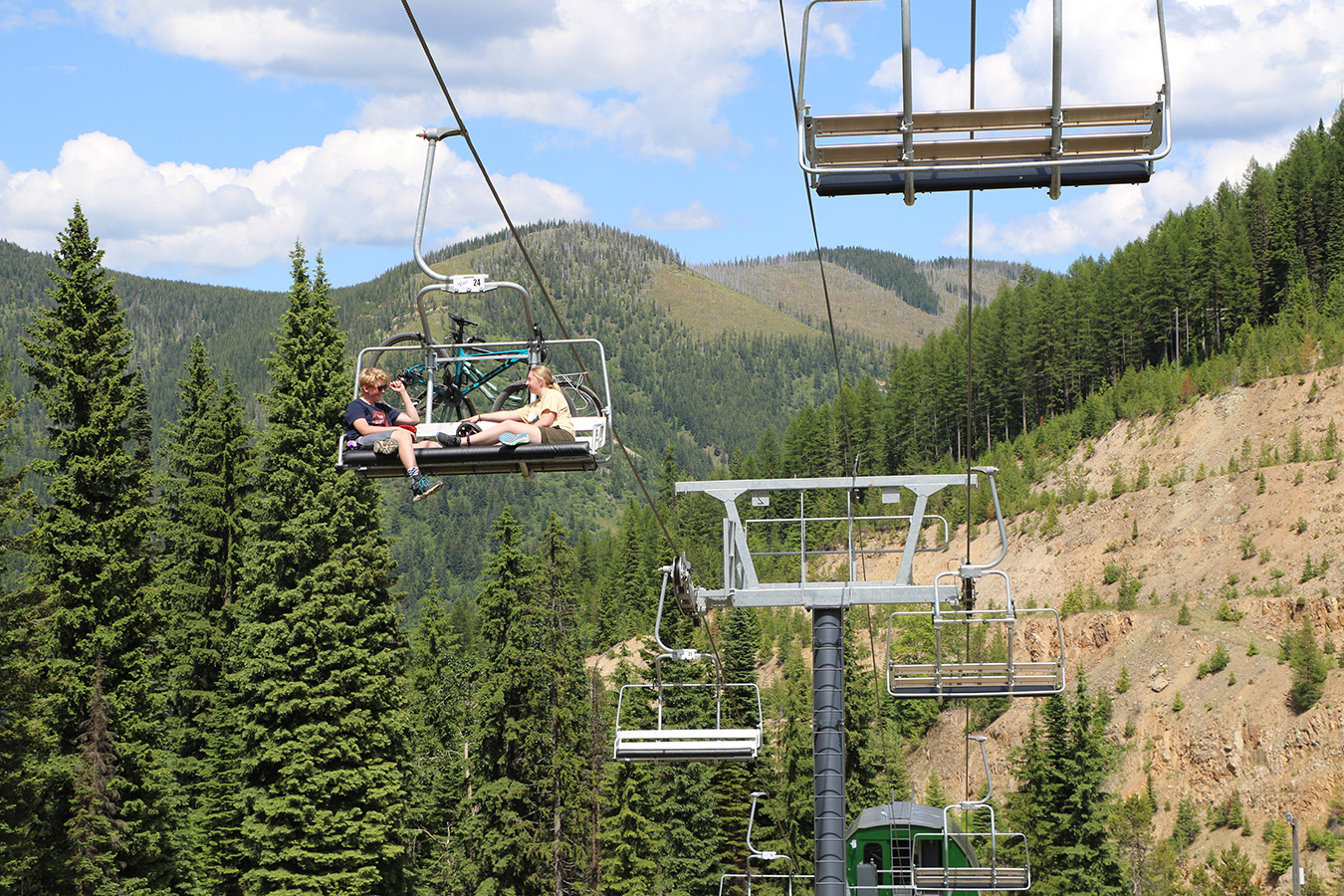 People riding a chairlift at Lookout Pass during summer to access hiking and mountain biking trails.