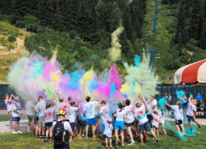 Parents and children enjoying the Huckleberry Color Fun Run at Schweitzer, with colored chalk in the air.
