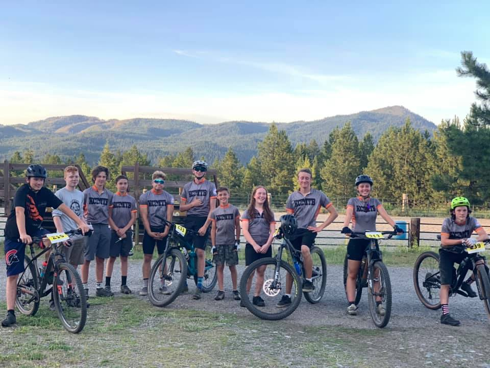 Group of teen and pre-teen bike riders in Colville, with view of hills and trees in background.