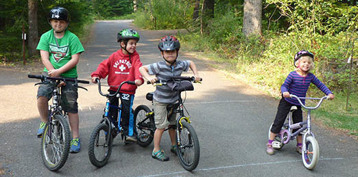 Three boys and girl on their bikes ready to ride the campground loop road.