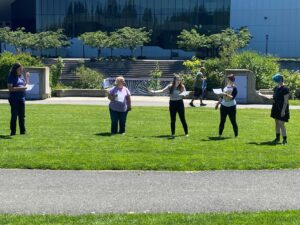 Actors standing on the grass rehearsing for Shakespeare in the park.