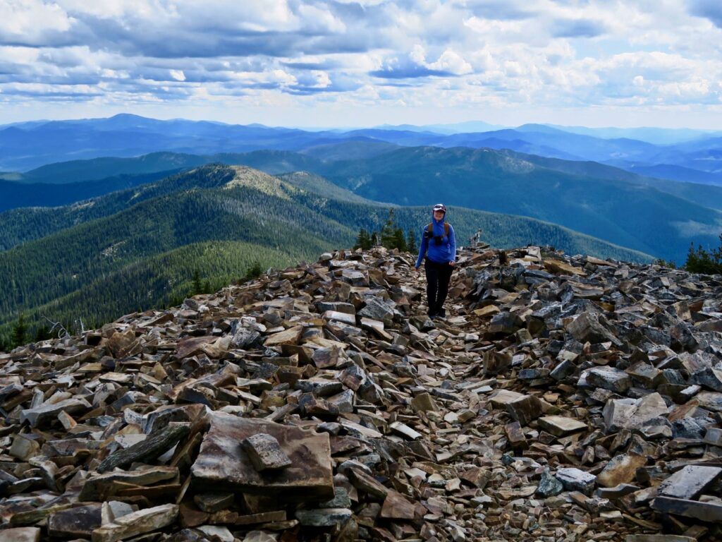 Hiker standing atop shale rocks on the summit of Abercrombie Mountain.