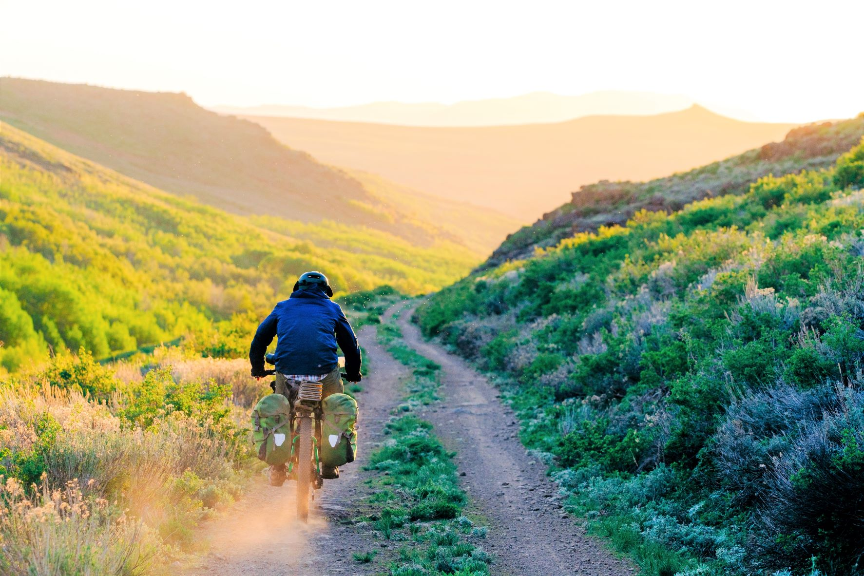 Bikepack riding a gravel road on Oregon's Big Country Route, alongside sagebrush.
