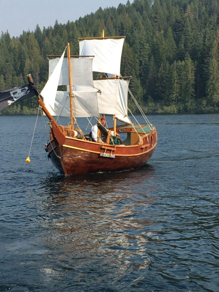 Pirate boat on Lake Pend Oreille, with white sails and wooden hull, with Captain Dan steering.