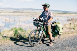 Derrick Knowles on his mountain bike, loaded with gear for bikepacking.