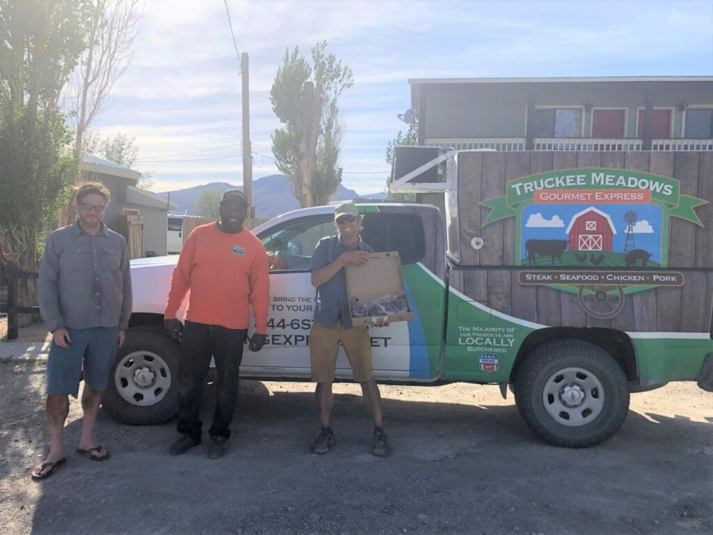 Two men standing beside the driver and beside the Truckee Meadows Gourmet Express truck.