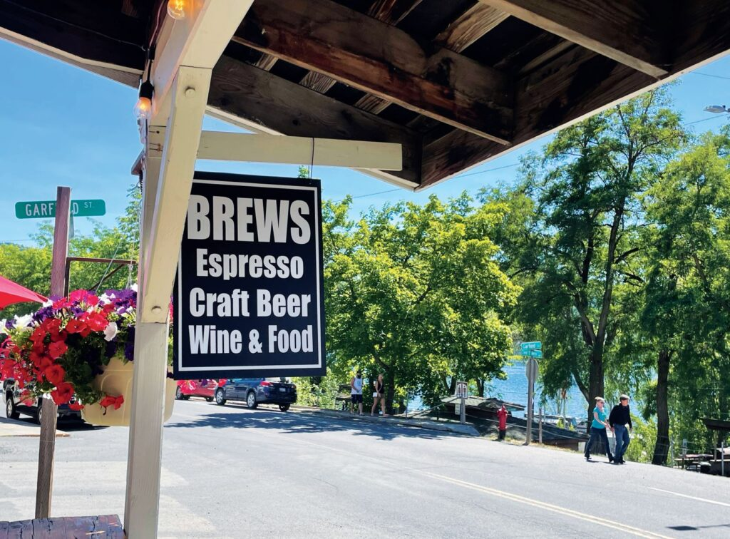 """Wooden sign outside a cafe in Harrison, Idaho, that reads """"Brews, Espresso, Craft Beer, Wine & Food."""""""